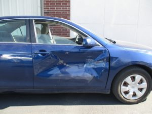 blue car with a big dent in passenger door