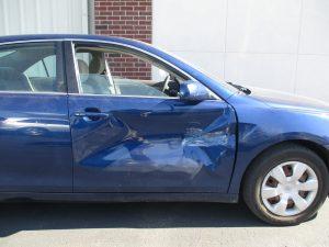 blue car with a big dent in passenger door