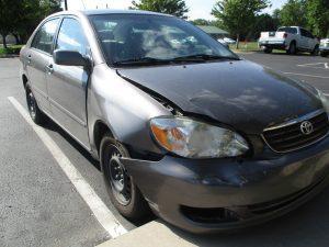 dented fender on a dark Corolla