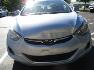 silver car with dented hood