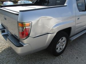dent on back of silver Honda truck