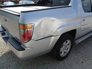 dent on back of silver Honda truck