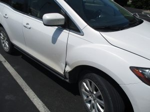 dent to door and surrounding area of a white SUV