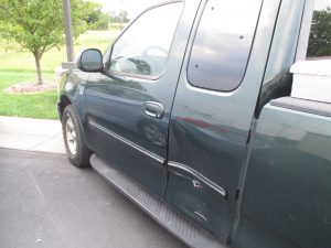 side impact damage to a green Ford truck
