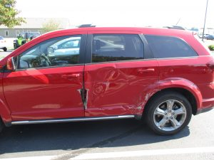 lots of damage to side of a red SUV