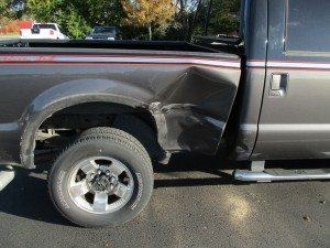 gray truck with large dent in side