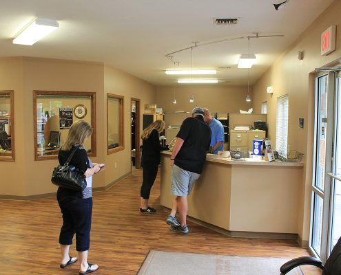 Customers at the front desk inside Collision Center. Our friendly and professional staff will help get you the auto body work you need, serving the Wichita area.