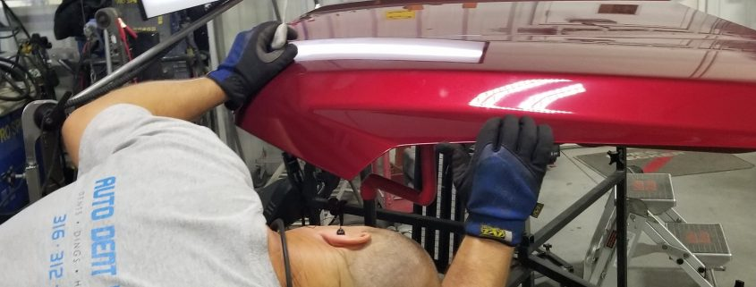 Paintless dent repair work. Collision Center of Andover technician working on the hood as part of our full service auto body and collision repair work. We handle restoration and glass replacement and more for the Wichita area.