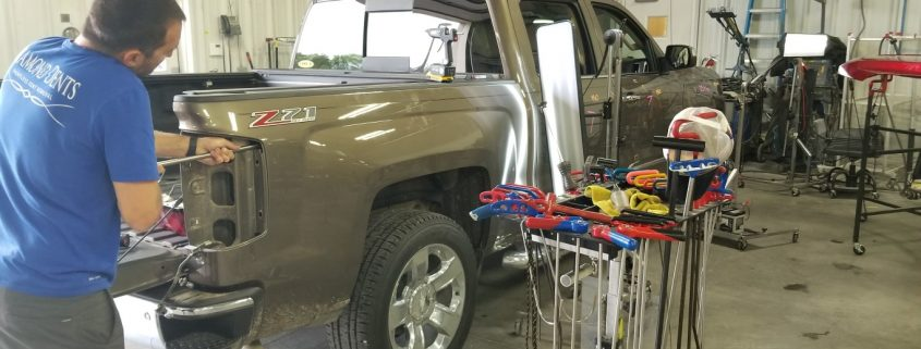 Collision Center of Andover technician working on an auto body repair to handle paintless dent repair on a gold truck.
