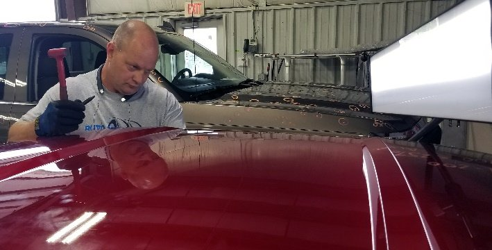 repair technician working on roof of vehicle