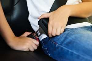 a child putting on their seat belt inside a vehicle