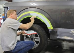 Collision Center tech doing paint job on truck in Andover auto shop