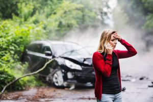 Woman on the phone looking distressed with a very damaged vehicle behind her tangled up in a tree