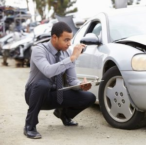 Photo of an insurance adjuster inspecting damage on a vehicle with a flashlight