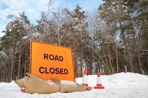 Road closed sign with traffic cones at a country highway covered in snow