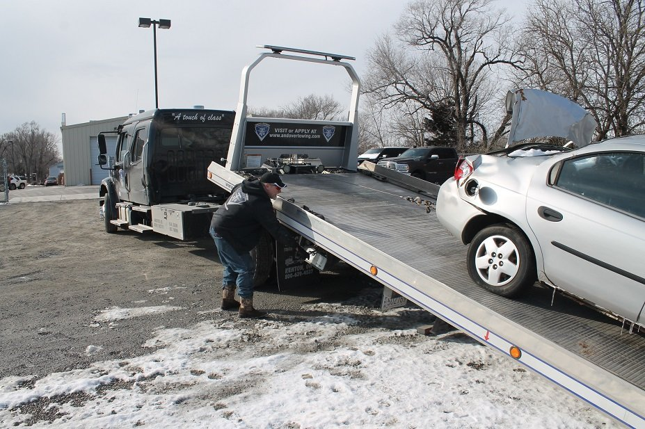 Tow truck carrying damaged car. Towing services from Collision Center of Andover, serving entire Wichita area.