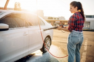woman cleaning her white car with a hose because a dirty vehicle is a bad driver habit