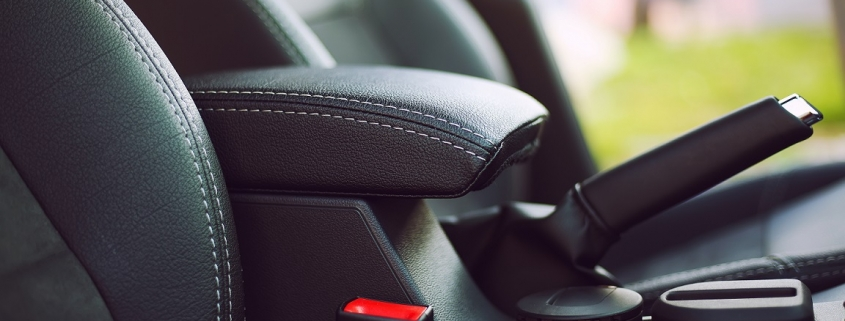 Parking brake engaged inside a vehicle with black leather interior, not doing so is a common bad habit for drivers