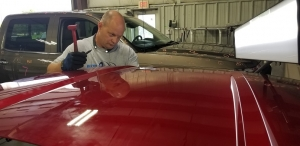 Collision Center of Andover auto body technician doing PDR to fix dings