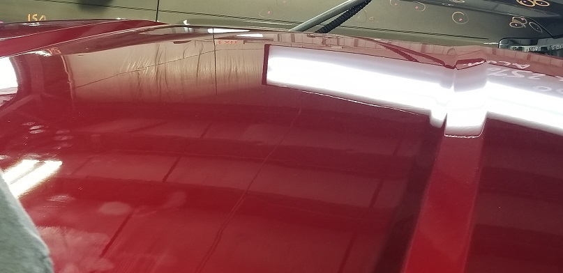 Shiny smooth red car hood fixed using paintless dent repair