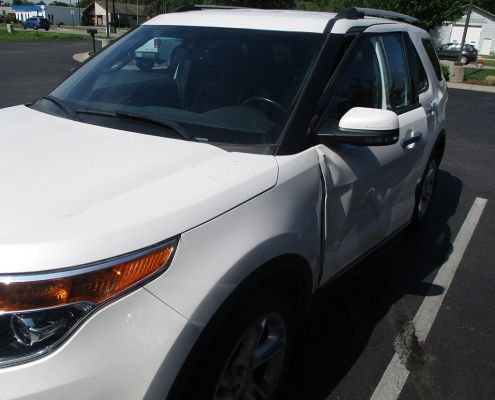 White Ford Explorer SUV in Andover parking lot with car door dings